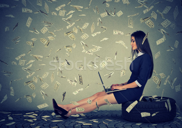 woman using a laptop building online business under money rain Stock photo © ichiosea