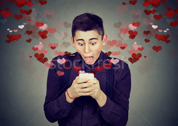 shocked man receiving love sms text message on mobile phone  Stock photo © ichiosea