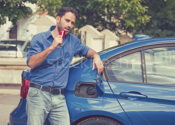 Handsome man with credit card opening fuel tank of new car Stock photo © ichiosea