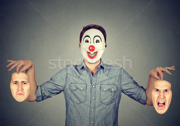 Man in happy clown mask holding two faces expressing anger and sadness  Stock photo © ichiosea