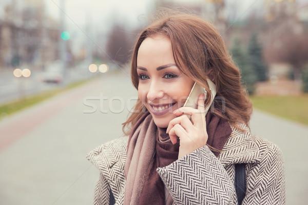 Content woman having phone call on street Stock photo © ichiosea