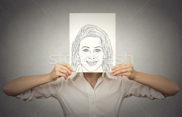 Beautiful woman with happy self portrait in front of her face, hiding true emotions Stock photo © ichiosea