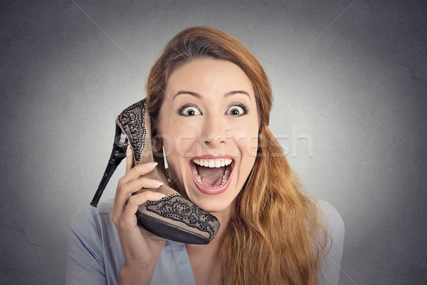 Headshot happy woman looking excited holding high heeled shoe as phone  Stock photo © ichiosea
