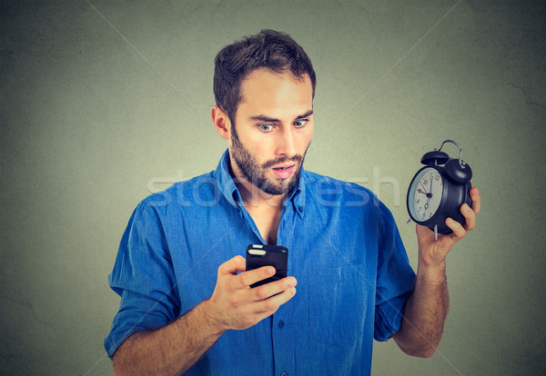 perplexed business man with alarm clock looking at smart phone  Stock photo © ichiosea