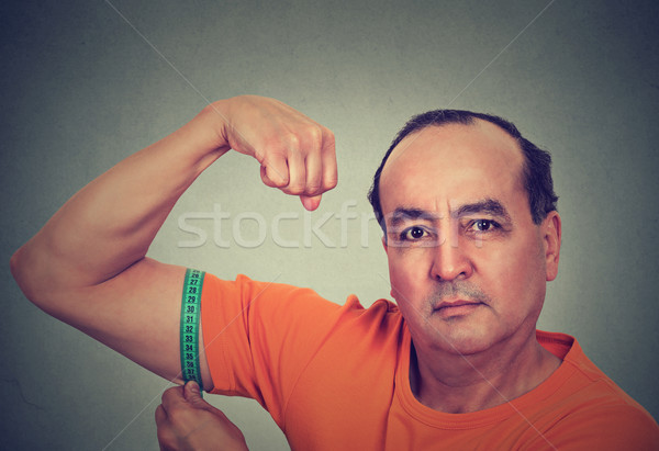 Man flexing his muscle measuring his biceps. Fitness goal achievement result  Stock photo © ichiosea