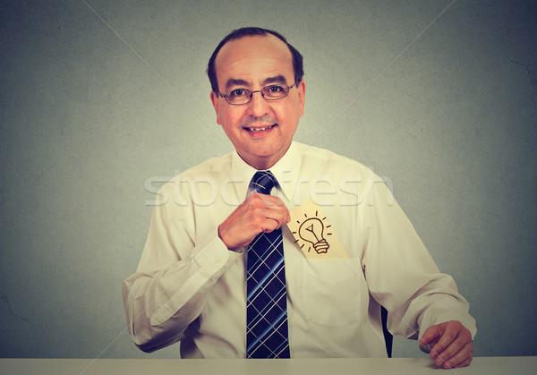 businessman with a great idea withdrawing a card with light bulb from his shirt pocket Stock photo © ichiosea