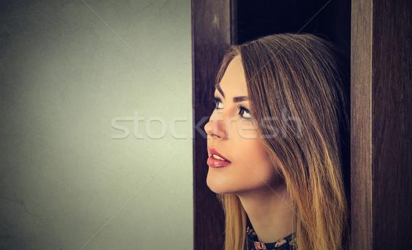 Woman wondering looking who's behind the door? Stock photo © ichiosea
