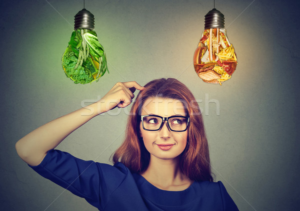 Woman thinking deciding on diet looking up at junk food vegetables light bulbs Stock photo © ichiosea