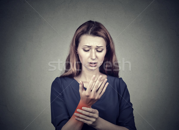 woman holding her painful wrist. Sprain pain location indicated by red spot.  Stock photo © ichiosea