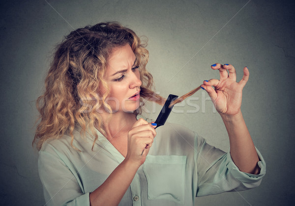 Stock photo: frustrated woman surprised she is losing hair split ends