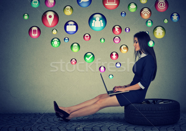 Woman working on laptop application icons flying out of screen  Stock photo © ichiosea