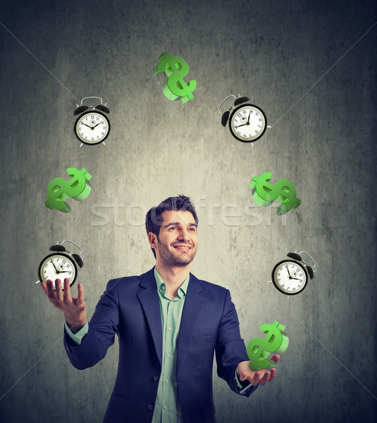 Time is money. Businessman juggling dollar signs and alarm clock  Stock photo © ichiosea