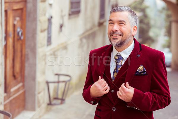 portrait of a middle age elegant business man standing outdoors on a street of an old village Stock photo © ichiosea
