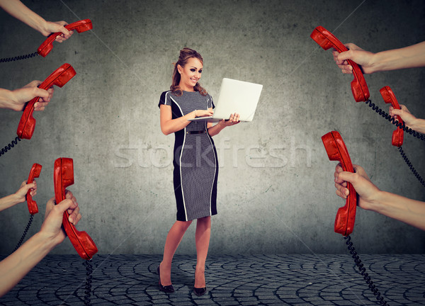 beautiful businesswoman with laptop surrounded by many hands with phone headsets  Stock photo © ichiosea