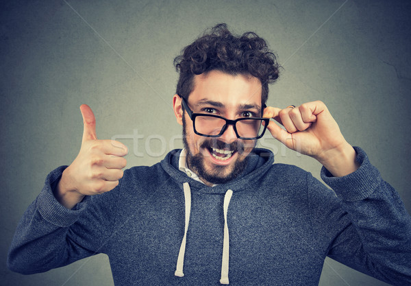 handsome man in glasses and hoodie holding thumbs up Stock photo © ichiosea