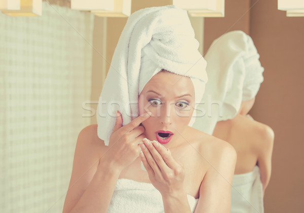 Surprised middle aged woman looking in mirror unhappy with wrinkles on face Stock photo © ichiosea