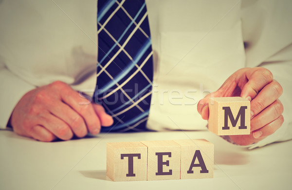 business man arranging cubes reading Team on table. Power of cooperation partnership concept  Stock photo © ichiosea