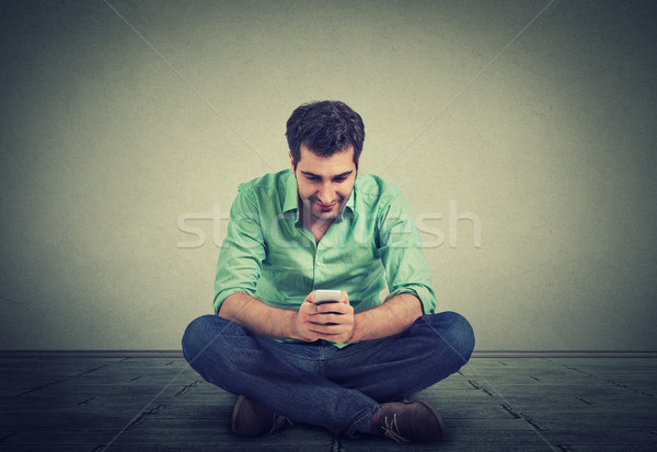 Happy man using texting on smartphone sitting on floor of his apartment Stock photo © ichiosea
