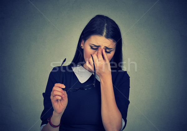 Stock photo: Woman with glasses rubbing her eyes feels tired
