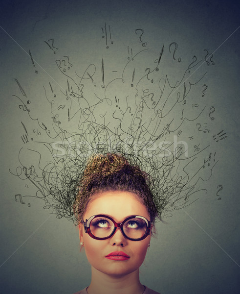 woman wondering, thinking daydreaming with brain melting into lines question marks looking up  Stock photo © ichiosea