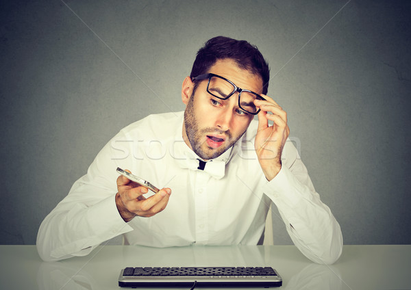 Shocked man talking on phone sitting at table with keyboard Stock photo © ichiosea