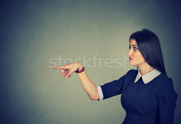 Stock photo: Displeased woman pointing finger at someone