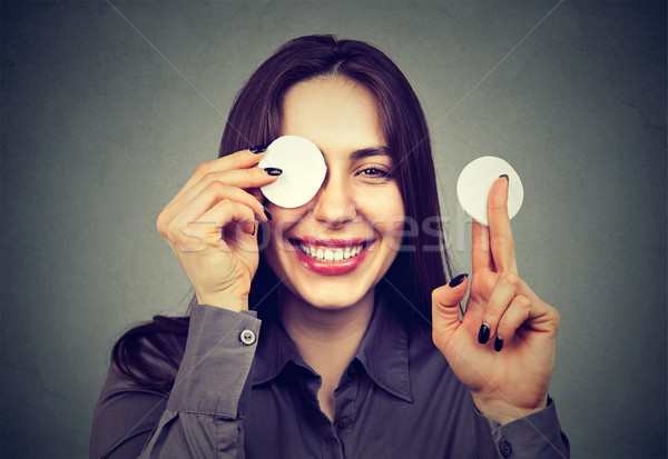 Cute woman removing applied makeup with a cotton sponge pad  Stock photo © ichiosea