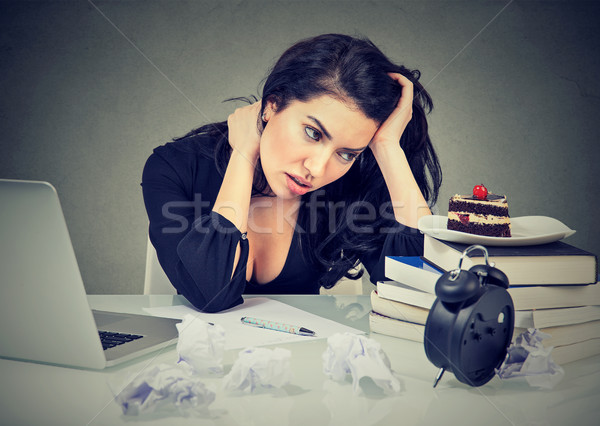 Stock photo: stressed woman sitting at desk in her office overworked craving sweet cake