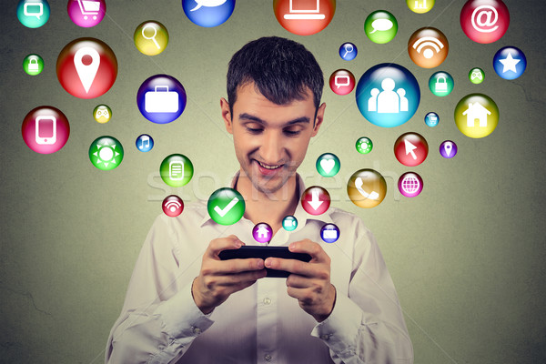 Happy man using texting on smartphone social media application icons flying up Stock photo © ichiosea