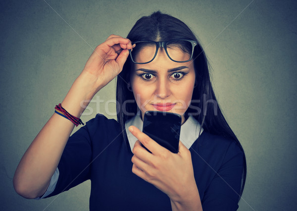 Young upset confused woman with glasses looking at mobile phone Stock photo © ichiosea