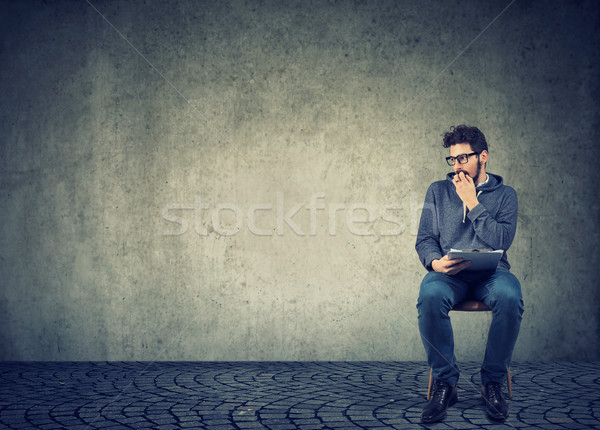 Anxious man sitting with resume anticipating interview, feeling nervous Stock photo © ichiosea
