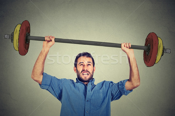 young business man trying to lift very heavy weight. Stock photo © ichiosea