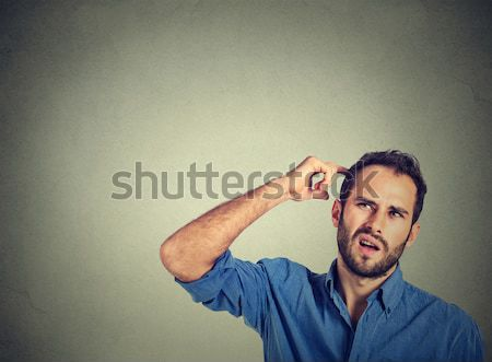 angry mad man gesturing with finger against temple are you crazy? Stock photo © ichiosea