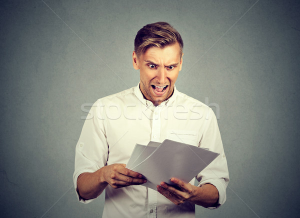 Angry businessman with documents  Stock photo © ichiosea