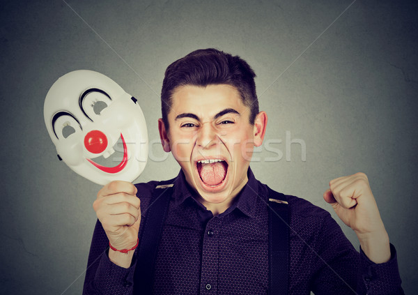 Upset angry screaming man holding clown mask expressing cheerfulness Stock photo © ichiosea