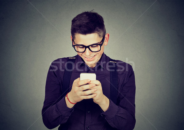 Smiling young man text messaging on mobile phone  Stock photo © ichiosea