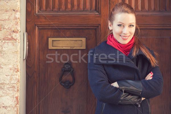 Portrait of attractive woman in front of old wooden door Stock photo © ichiosea