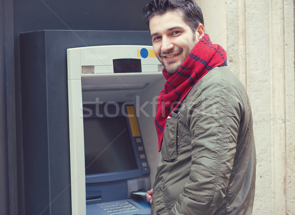 Content man using ATM machine outside Stock photo © ichiosea
