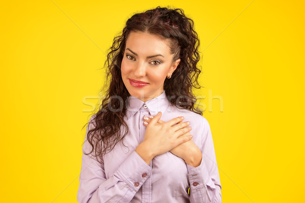 Faithful woman keeps hands on chest near heart, shows her kindness Stock photo © ichiosea