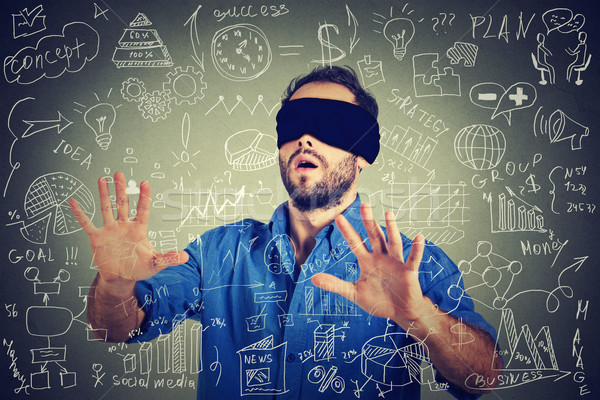 Blindfolded young business man searching walking through social media financial data plan Stock photo © ichiosea