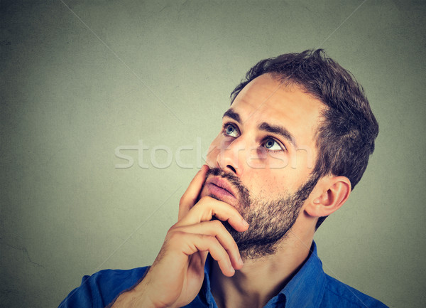 man resting chin on hand thinking daydreaming, staring thoughtfully upwards Stock photo © ichiosea