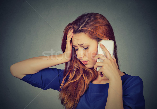 Portrait unhappy young woman talking on mobile phone looking down Stock photo © ichiosea