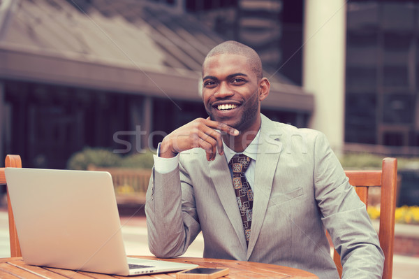 Cheerful business man sitting at table with laptop outside corporate office  Stock photo © ichiosea
