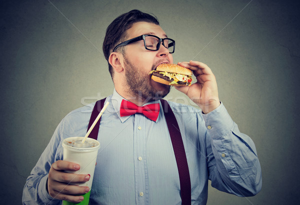 Overweight business man eating with appetite a burger holding a can of soda drink  Stock photo © ichiosea