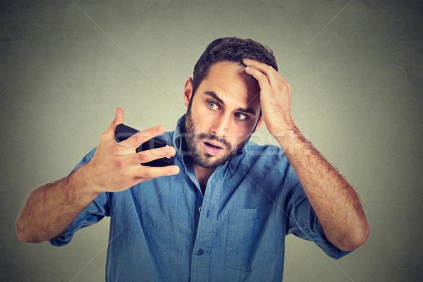 portrait, shocked man feeling head, surprised he is losing hair, receding hairline Stock photo © ichiosea