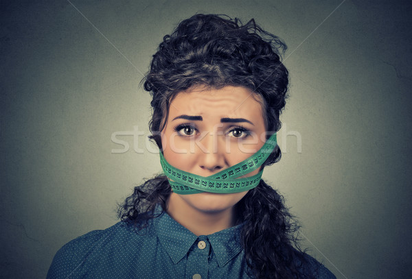 Diet restriction and stress concept. Frustrated woman with measuring tape around her mouth Stock photo © ichiosea
