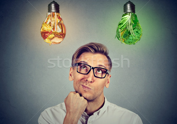 Man thinking looking up at vegetables light bulbs craving junk food  Stock photo © ichiosea