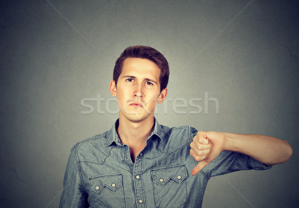 angry young man showing thumbs down sign, in disapproval  Stock photo © ichiosea