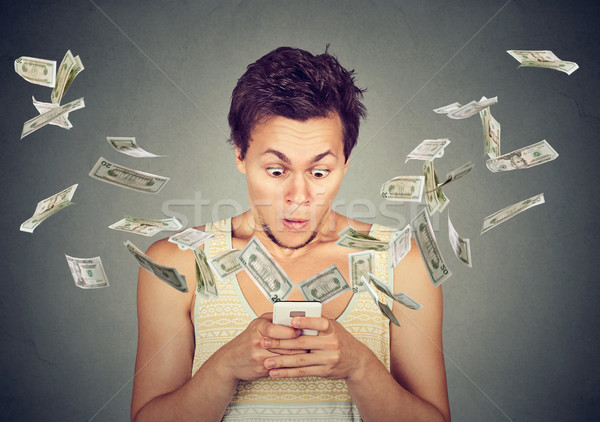 Stock photo: surprised man using smartphone dollar bills flying away from screen