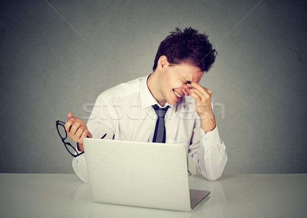 Stock photo: Tired business man rubbing his eye sitting at table with laptop